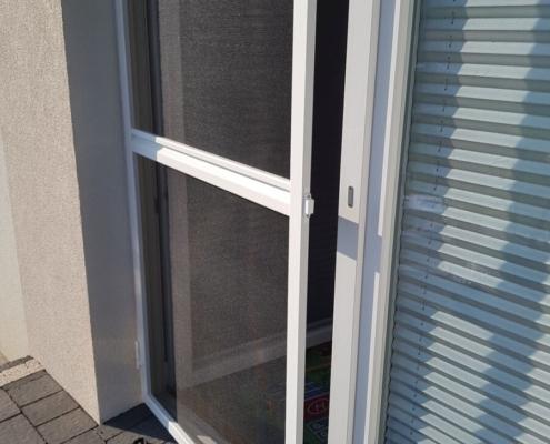 Uchylona moskitiera ramkowa zamontowana na drzwiach balkonowych