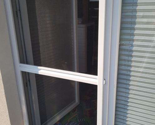Biała moskitiera ramkowa zamontowana na oknie balkonowym